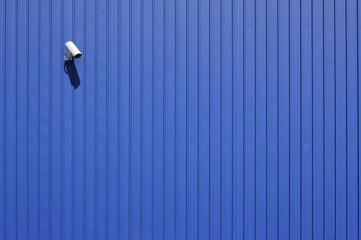 cctv video surveillance camera on blue metallic wall