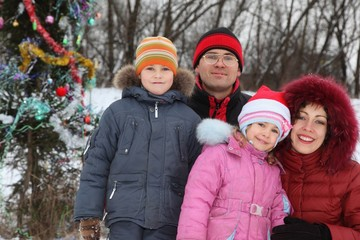 family with two children near christmass tree.