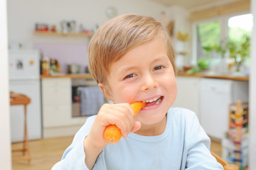 Kind beisst in eine Karotte