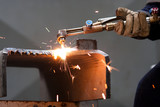 worker inside factory cut metal using blowtorch poster