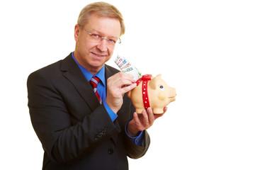 Geschäftsmann steckt Banknoten in Sparschwein