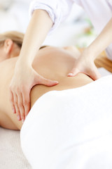 Close-up of a caucasian woman receiving a back massage