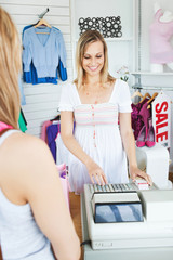 Positive saleswoman standing behind the counter using the cash r
