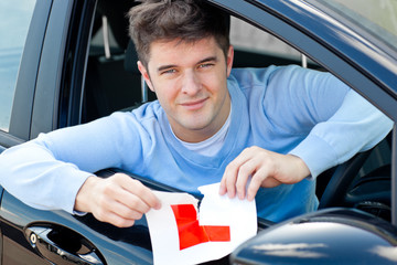 """Happy young man tearing a """"L"""" sign sitting in his car smiling"""
