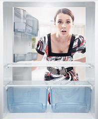 Young woman looking on empty shelf in fridge