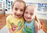 Two Female Primary Schoolchildren In Classroom poster
