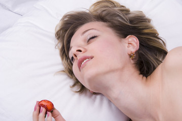 Young woman lying down with sex toys on a bed