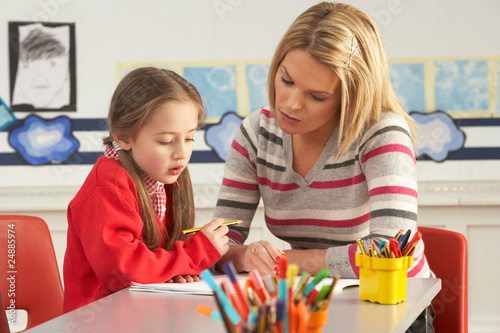 Leinwanddruck Bild Female Primary School Pupil And Teacher Working At Desk In Class