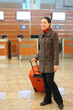 attractive woman with red suitcase standing at airport