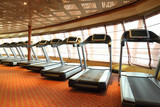 large gym hall with treadmills near windows in cruise ship