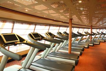 gym hall with  treadmills near windows in cruise ship