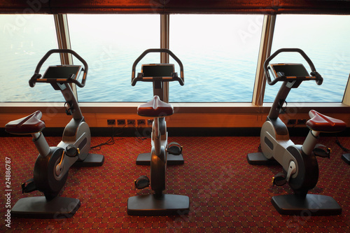 large gym hall with exercise bicycle near window