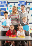 Portrait Of Group Of Primary Schoolchildren And Teachers Sitting poster