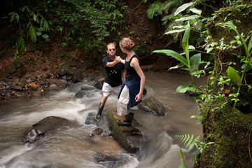 Woman helping man cross Costa Rican river