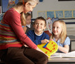 Female Teacher In Primary School Teaching Children To Tell Time