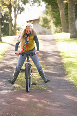 Portrait Of Young Woman With Cycle In Autumn Park