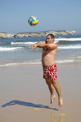 fat man playing with a ball on the beach