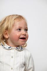 Fröhliches kleines Mädchen strahlt in die Kamera