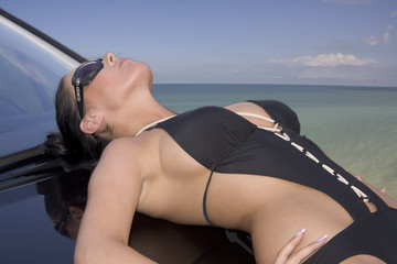 Junge Frau auf Auto am Meer