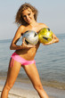 Sexy woman with two soccer balls on the beach
