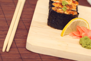 Sushi and rolls on the wooden plate