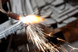 blowtorch cutting metal in factory and sparks poster