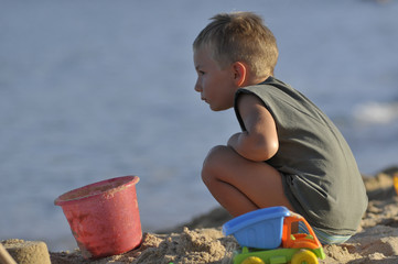 Pensive little boy at the beach