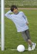 Junge mit Fussball, lächelnd , am Tor angelehnt