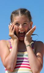 Девочка с телефоном на фоне голубого неба