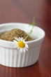 Chamomile flower on a white bowl with dry chamomile tea