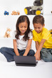 eastern siblings playing on laptop