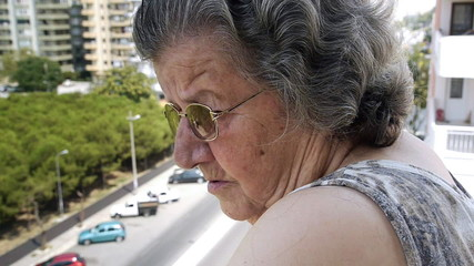 Old retired woman watching traffic from balcony