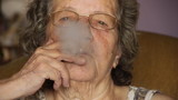 Old retired woman smoking cigarette - Unhealthy poster