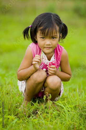 cute asian girl holding a grasshopper