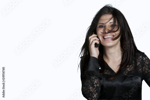 Young woman with messy hair on the phone, studio shot