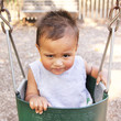 Little baby boy in swing making funny face