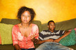 African-american woman and teen sit on sofa