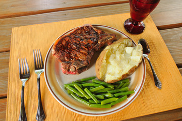 Dinner setting with steak, green beans, and baked potato