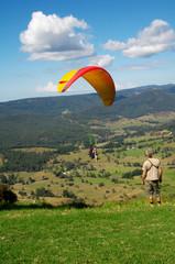 Tandem paragliders landing on grass slope