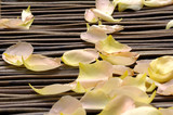 withered rose petals on bamboo mat poster