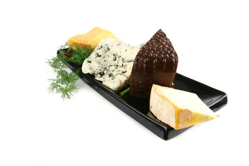 aged cheeses on black plate