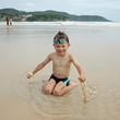 A la plage : Enfant jouant avec le sable