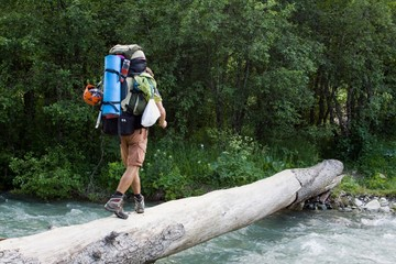 Backpacker crossing the river.