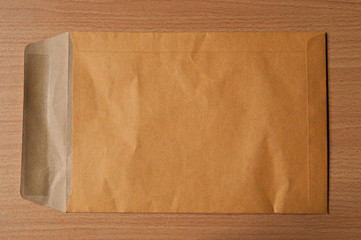 Open Brown Envelope document on wood background