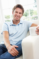 Man Sitting On Sofa Drinking Coffee Relaxing At Home