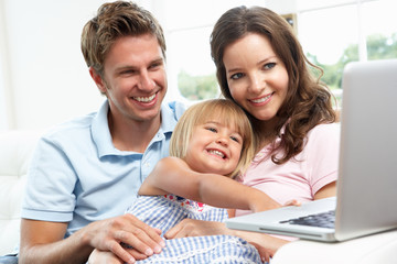 Family Sitting On Sofa Using Laptop At Home