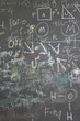 grey school chalkboard with many different formuls, signs and co
