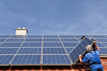 Workmen assembling solar paneels