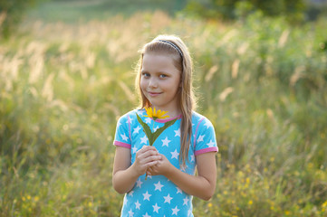 Little smiling girl with yellow flower