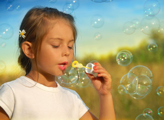 Dreams, little girl blowing soap bubbles at sunset